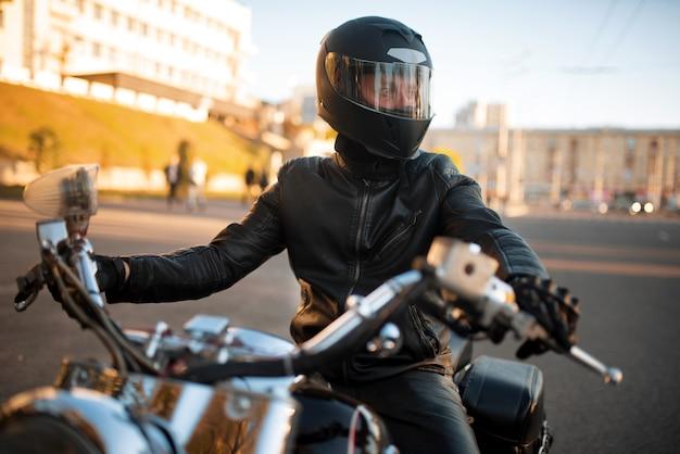 Biker in lederjacke und helm mit visier sitzt auf klassischem chopper.