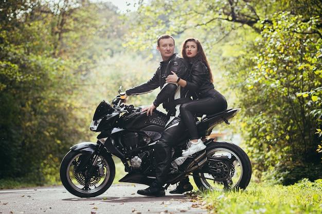 Biker in lederkleidung, mann und frau, sitzen auf einem schwarzen sportmotorrad im wald
