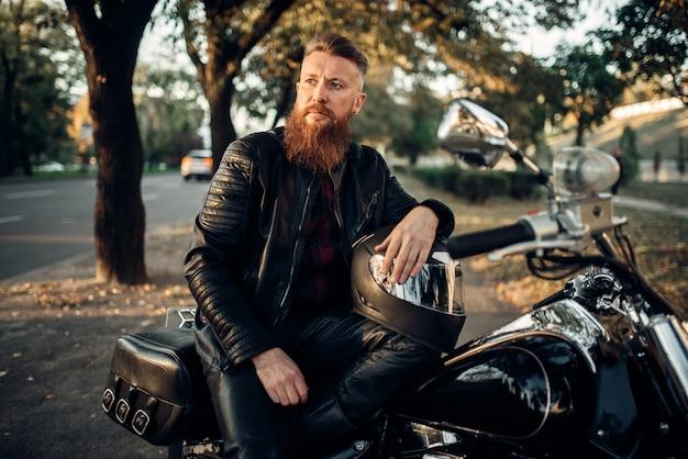 Biker sitzt auf dem boden gegen seinen hubschrauber