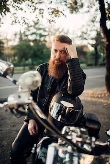 Biker sitzt auf einem motorrad und lehnt sich an einen helm. vintage fahrrad, fahrer und sein zweirädriger freund, freiheit lebensstil, radfahren
