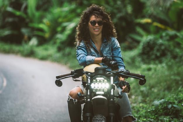 Bikerin, die ein cafe racer motorrad fährt