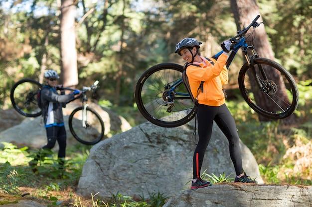 Bikerpaar hält ihr mountainbike und geht in wald