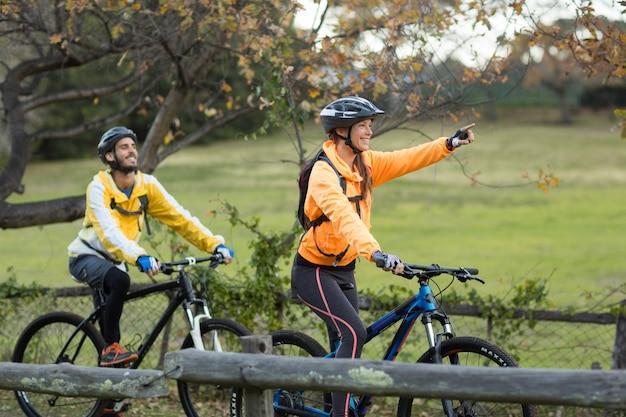 Bikerpaar radfahren und in die ferne zeigen