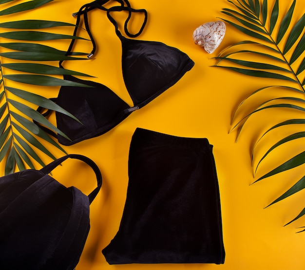 Bikini-badeanzug aus schwarzem samt, sportgamaschen und rucksack mit tropischen palmblättern. draufsicht.