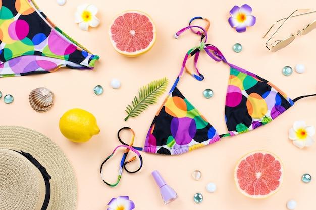 Bikini-badeanzug mit strohhut, blumen und früchten, flaches design, sommerkonzept. stranddestination, sommermode