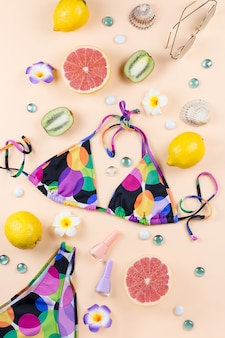 Bikini-badeanzug mit strohhut, blumen und früchten, sommerkonzept. stranddestination, sommermode
