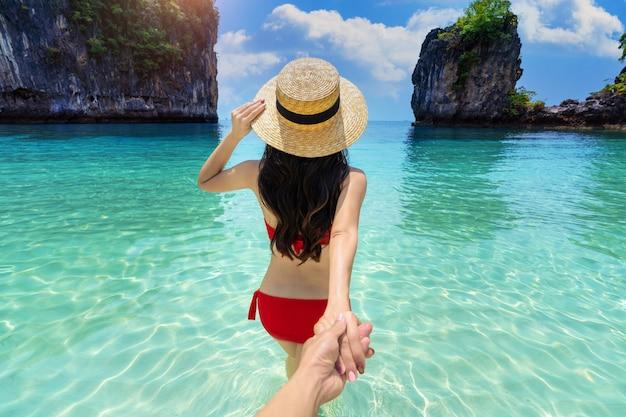 Bikini-mädchen, das die hand des mannes hält und ihn zur insel koh hong in krabi, thailand, führt