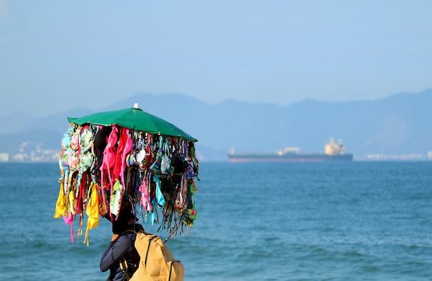 Bikini-verkäufer, der viele bikinis geht auf copacabana-strand, rio de janeiro, brasilien trägt
