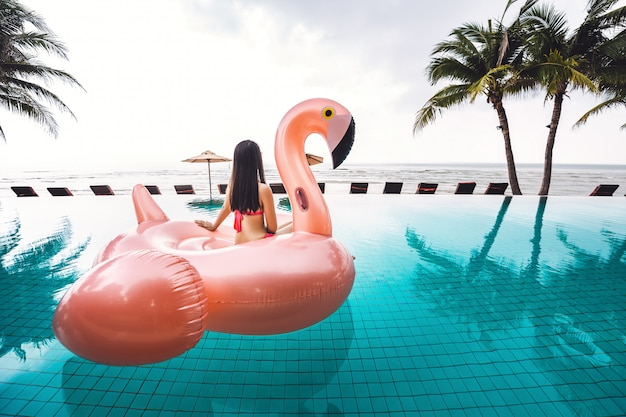 Bikinifrauenentspannung auf poolfloss