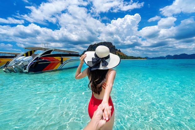 Bikinimädchen, das die hand des mannes hält und ihn zum ozean in krabi, thailand führt
