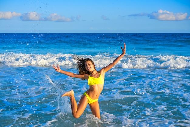 Bikinimädchen, das in karibischen sonnenuntergangstrand springt