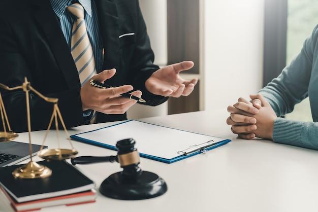 Bild anwalt geschäftsmann sitzt im büro mit einer kundin, die die beratungsvereinbarung erklärt.