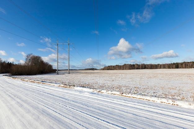 Bild aufgenommen im winter nach schneefall auf einer kleinen landstraße. schnee auf dem boden