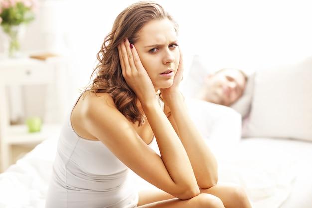 Bild, das junge frau und ihren mann zeigt, die ein problem im schlafzimmer haben