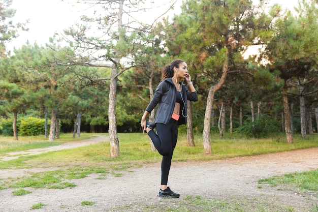 Bild der afroamerikanerfrau 20s, die schwarzen trainingsanzug trägt, der sport macht und ihren körper im grünen park streckt