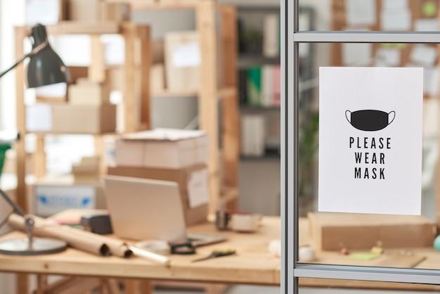 Bild der anzeige mit text, zum der maske zu tragen, die an glaswand im büro hängt