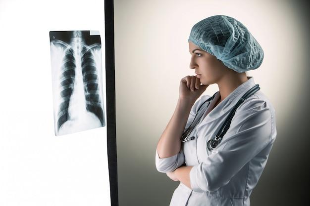 Bild der attraktiven ärztin, die röntgenergebnisse betrachtet