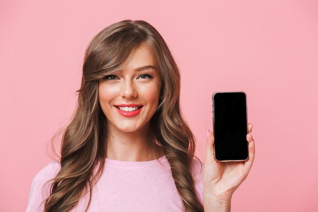 Bild der attraktiven frau, die schönes langes haar hält handy in händen hält und schwarzen bildschirm des copyspace auf kamera demonstriert, lokalisiert über rosa hintergrund
