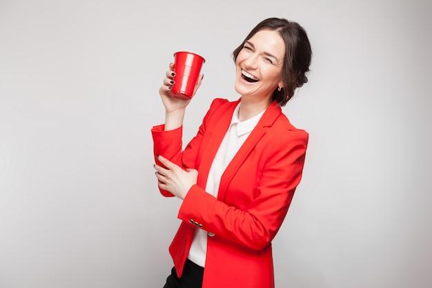 Bild der attraktiven frau im roten kleid mit tasse bier in den händen
