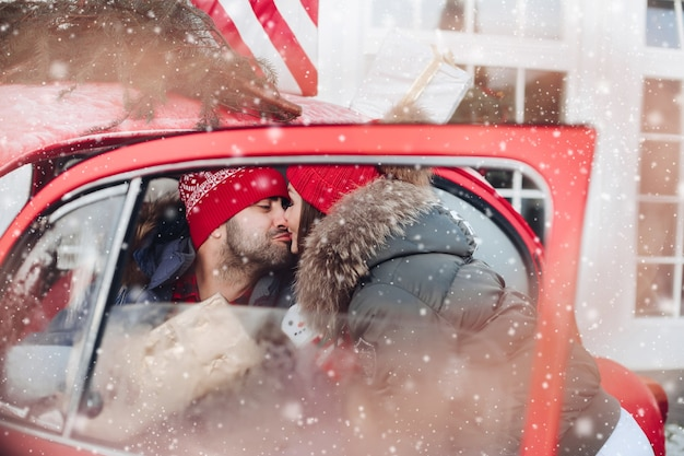 Bild der attraktiven kaukasischen frau in der warmen kleidung trägt kisten mit weihnachtsgeschenken in einem auto zu ihrem freund und küsst ihn