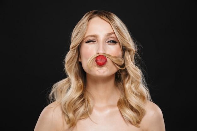 Bild der aufgeregten jungen schönen emotionalen frau mit den roten lippen des hellen make-ups, die lokalisiert aufwerfen.