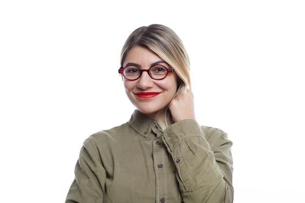 Bild der bezaubernden jungen frau in der stilvollen brille, die mit niedlichem lächeln schaut und glücklichen freudigen ausdruck auf ihrem hübschen gesicht hat. attraktive weibliche werbeoptik mit runder brille