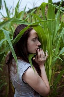 Bild der bezaubernden jungen kaukasischen frau mit dunklem haar im grauen sommerkleid