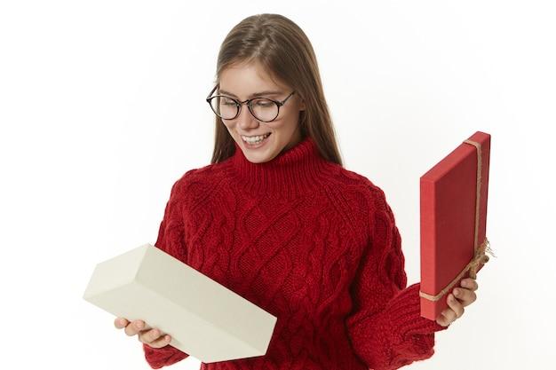 Bild der ekstatischen schönen jungen frau, die brille und gemütliche pulloveröffnungsgeschenkbox trägt
