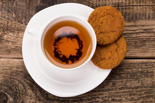 Bild der elfenbein-teetasse mit süßem keks auf holzpalette