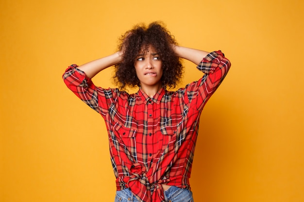 Bild der emotionalen jungen afrikanischen frau, die lokalisiert über orange hintergrund aufwirft. überraschungsgesicht. studioaufnahme.