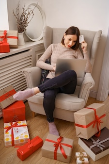 Bild der erfreuten netten frau, die kreditkarte mit kopienraum unter verwendung des laptops hält