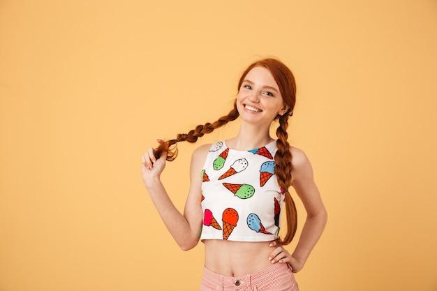 Bild der erfreuten schönen rothaarigen frau, die im eiscreme-bedruckten t-shirt gekleidet wird, das lokalisiert über gelber wand aufwirft.