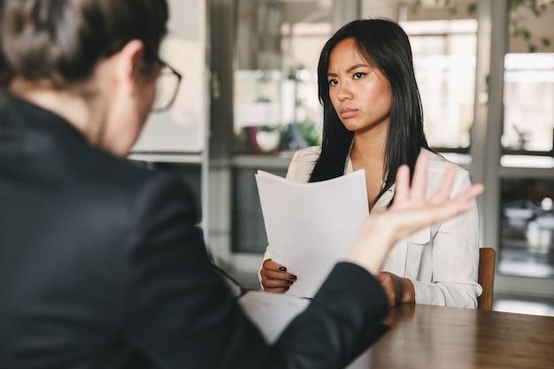 Bild der ernsthaften asiatischen frau, die geschäftsfrau schaut und spricht, während sie während des vorstellungsgesprächs am tisch im büro sitzt - geschäfts-, karriere- und rekrutierungskonzept