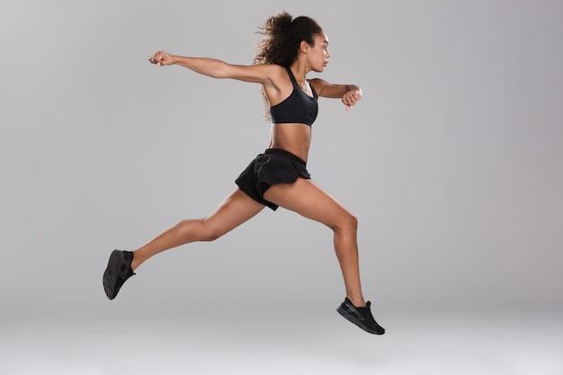 Bild der erstaunlichen schönen starken sportfrau, die isoliert springt.