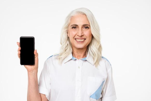 Bild der erwachsenen frau mit dem grauen haar, das lächelt und werbung mit dem präsentieren des mobiltelefons tut, lokalisiert über weißer wand