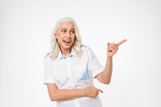 Bild der erwachsenen frau mit grauem haar, das lächelt und mit gestikulierendem finger auf kopienraum beiseite schaut, lokalisiert über weißer wand