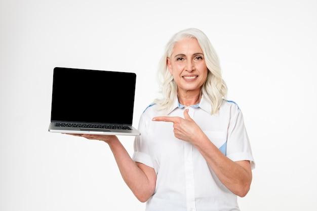 Bild der erwachsenen frau mit grauem haar lächelnd und zeigefinger auf copyspace-bildschirm des laptops, lokalisiert über weißer wand