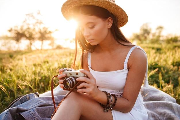 Bild der europäischen brünetten frau mit dem langen haar, das strohhut und weißes kleid hält retro-kamera beim sitzen auf gras im park während der freizeit trägt