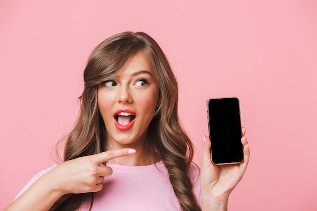 Bild der europäischen frau, die schöne braune schlösser hält, die handy in händen halten und finger auf schwarzen bildschirm des copyspace zeigen, lokalisiert über rosa hintergrund