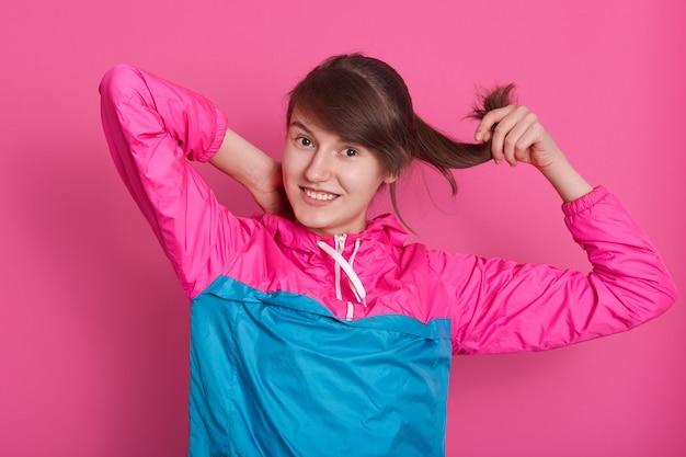 Bild der fitnessfrau, die im studio über rosa steht