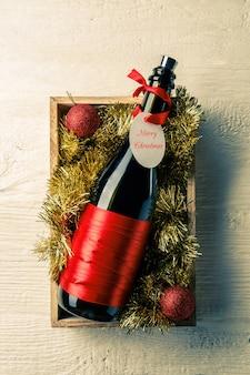 Bild der flasche wein mit karte in der holzkiste mit lametta, weihnachtskugeln auf weißem tisch
