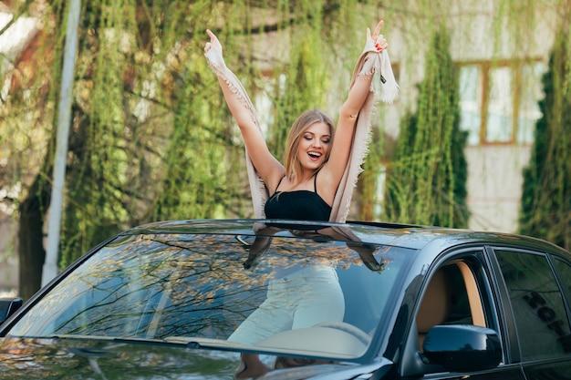 Bild der fröhlichen jungen frau, die sonnenbrille und erhobene hände auf dem schiebedach des luxusautos trägt
