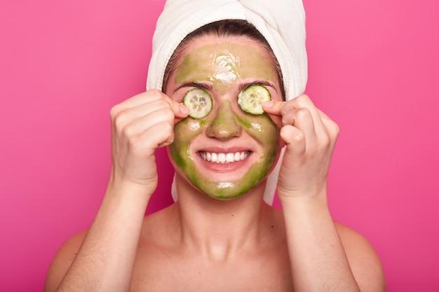 Bild der fröhlichen jungen frau hat grüne maske auf gesicht
