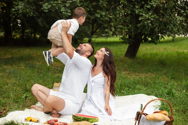 Bild der fröhlichen jungen kaukasischen frau und des mannes hält ihr kind auf händen, lächelt und freut sich