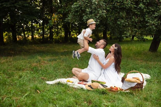 Bild der fröhlichen kaukasischen mutter, des vaters und ihres kindes haben spaß zusammen und lächelt im garten