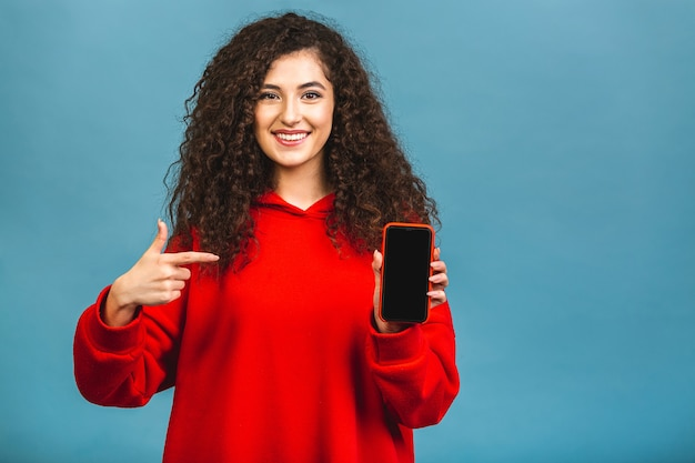 Bild der fröhlichen verblüfften jungen lockigen kaukasischen frau, die anzeige des mobiltelefons zeigt.