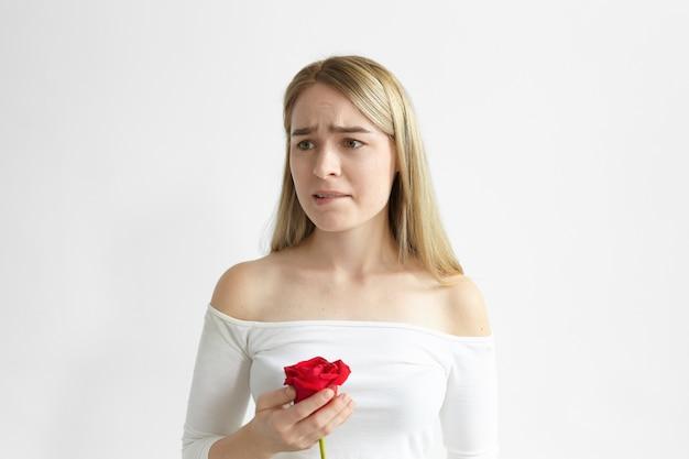 Bild der frustrierten schönen jungen dame, die mit einer roten rose von ihrem geliebten aufwirft, besorgt und verärgert ist, lippen beißt