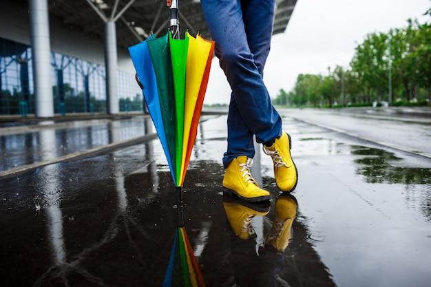 Bild der gelben schuhe des jungen geschäftsmanns 39 und des bunten regenschirms in der regnerischen straße