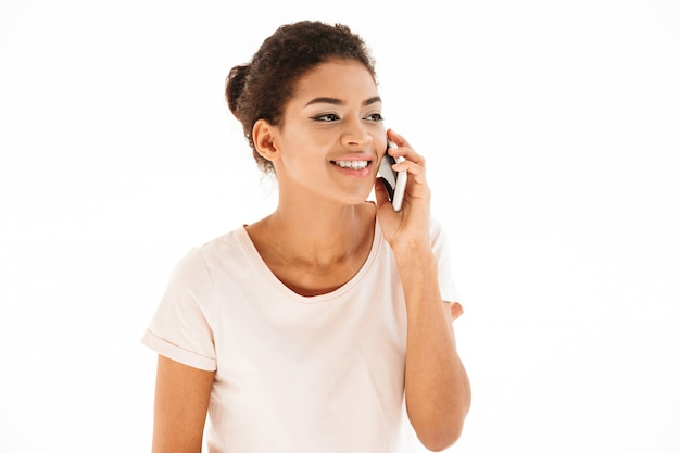 Bild der gemischten rassenfrau im lässigen blick beiseite und sprechend auf handy, lokalisiert über weißer wand