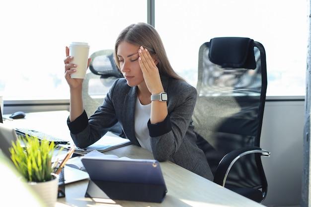 Bild der geschäftsfrau, die müde aussieht, während sie an ihrem arbeitsplatz sitzt und pappbecher in der hand hält.